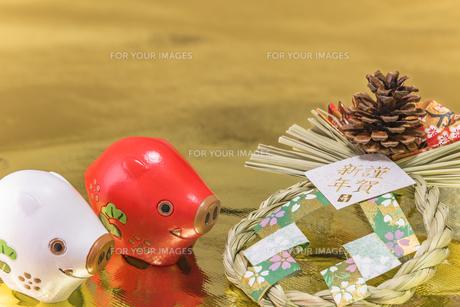 金箔の背景に謹賀新年と書いてある藁制のお正月の飾りと猪のフィギュアの写真素材 [FYI01226186]