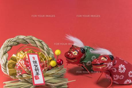 赤い背景に謹賀新年と書いてある藁制のお正月の飾りと獅子舞のフィギュアの写真素材 [FYI01226194]