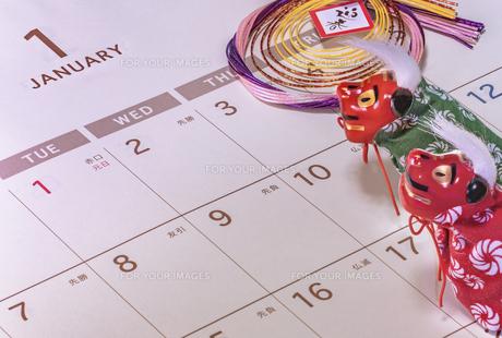 カレンダーの一月のページを背景に迎春と書いてあるお正月の飾りと獅子舞のフィギュアの写真素材 [FYI01226196]