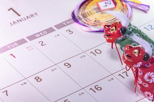 カレンダーの一月のページを背景に迎春と書いてあるお正月の飾りと獅子舞のフィギュアの写真素材 [FYI01226197]