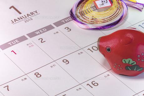 カレンダーの一月のページを背景に迎春と書いてあるお正月の飾りと猪のフィギュアの写真素材 [FYI01226198]