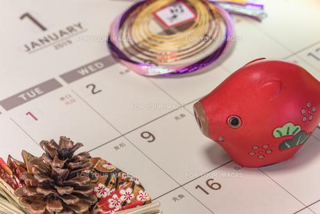 カレンダーの一月のページを背景に迎春と書いてあるお正月の飾りと松かさと猪のフィギュアの写真素材 [FYI01226199]