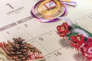 カレンダーの一月のページを背景に迎春と書いてあるお正月の飾りと松かさと獅子舞のフィギュアの写真素材 [FYI01226200]