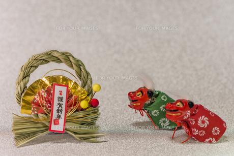 キラキラした銀色の背景に謹賀新年と書いてある藁制のお正月の飾りと獅子舞のフィギュアの写真素材 [FYI01226201]