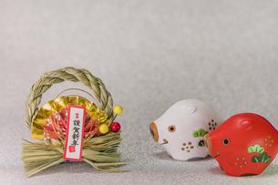キラキラした銀色の背景に謹賀新年と書いてある藁制のお正月の飾りと猪のフィギュアの写真素材 [FYI01226202]