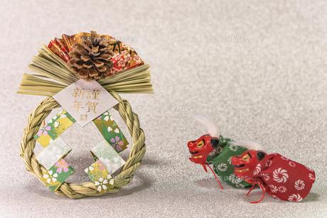 キラキラした銀色の背景に謹賀新年と書いてある藁制のお正月の飾りと獅子舞のフィギュアの写真素材 [FYI01226205]
