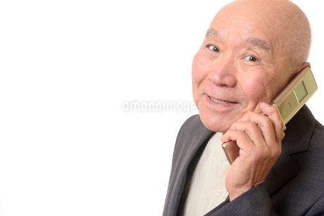 携帯電話をしている笑顔のビジネスマンシニアの写真素材 [FYI01226268]