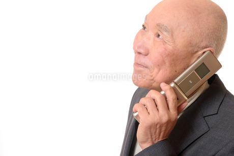 携帯電話をしている笑顔のビジネスマンシニアの写真素材 [FYI01226269]
