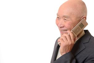 携帯電話をしている笑顔のビジネスマンシニアの写真素材 [FYI01226270]