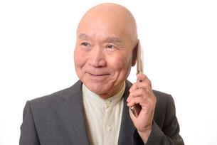 携帯電話をしている笑顔のビジネスマンシニアの写真素材 [FYI01226283]