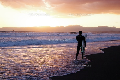 夕日を見るサーファーの写真素材 [FYI01226422]