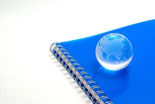 青いノートの表紙の上に置いたガラスの地球の写真素材 [FYI01226666]