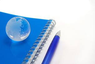 青いノートの表紙の上に置いたガラスの地球とボールペンの写真素材 [FYI01226667]