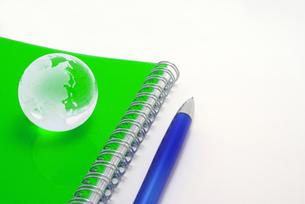 黄緑色のノートの上に置いたガラスの地球と白バックのボールペンの写真素材 [FYI01226668]