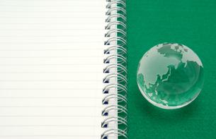 白いノートと緑背景のガラスの地球の写真素材 [FYI01226669]