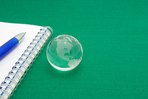 ノートの上に置いたボールペンと緑背景のガラスの地球の写真素材 [FYI01226670]