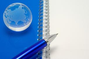 青いノートの表紙の上に置いたガラスの地球とボールペンの写真素材 [FYI01226671]