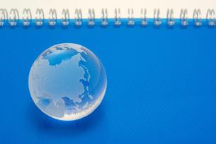青いノートの表紙の上に置いたガラスの地球の写真素材 [FYI01226672]