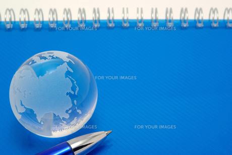 青いノートの表紙の上に置いたガラスの地球とボールペンの写真素材 [FYI01226673]