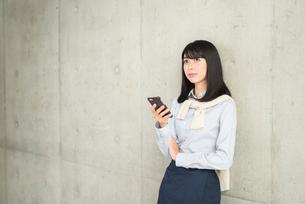 壁に寄りかかりiPhoneを片手で持ち画面を見ながら、前を見ている20代OL女性。の写真素材 [FYI01226693]