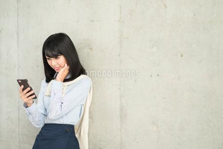 iPhoneを片手で持ち画面を見ながら、頬に手を当てて笑っている20代OL女性。の写真素材 [FYI01226694]