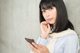 iPhoneを持ちながらこちらを見るOL女性。目線あり。顔の寄り。の写真素材 [FYI01226700]
