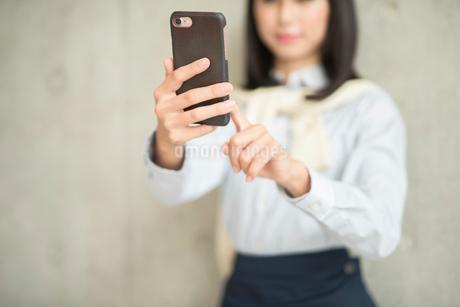 iPhoneを操作している女性(iPhoneにピント)の写真素材 [FYI01226704]