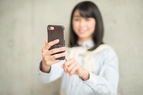 iPhoneを操作している笑顔の女性(iPhoneにピント)の写真素材 [FYI01226705]
