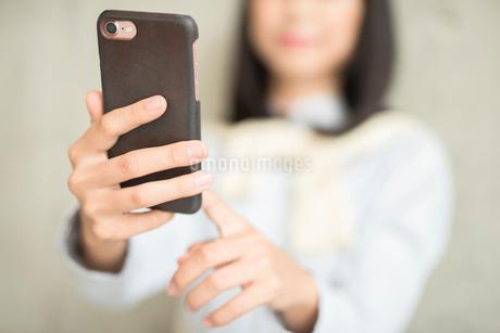 iPhoneを操作している女性の手元の寄り。指差し。の写真素材 [FYI01226707]