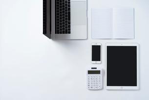 白背景の上にPC,iPhone,計算機,iPad,ノート。俯瞰構図。の写真素材 [FYI01226708]
