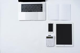 白背景の上にPC,iPhone,計算機,iPad,ノート。俯瞰構図。の写真素材 [FYI01226709]