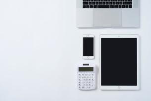 PCのキーボードとiPhoneと計算機とiPad。俯瞰構図。白背景。の写真素材 [FYI01226712]