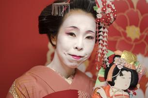 伝統的な羽子板を握る赤い着物を着た可愛い芸者あるいは舞子の姿の写真素材 [FYI01226799]