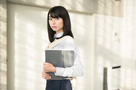 iPadを抱えこちらを見る20代OL女性の写真素材 [FYI01227296]