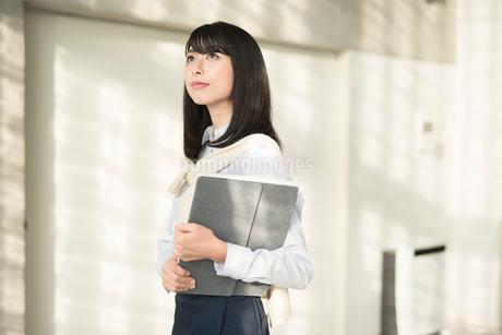 iPadを抱え上を見上げる20代OL女性の写真素材 [FYI01227297]