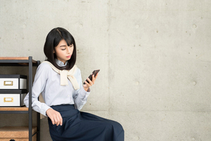座って棚に寄りかかりながらiPhoneを片手で操作する20代OL女性の写真素材 [FYI01227298]