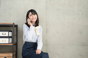 iPhoneで通話中の笑顔な20代OL女性の写真素材 [FYI01227302]