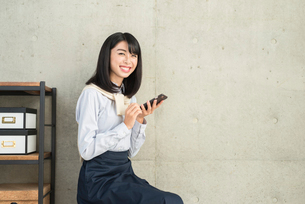 iPhoneを操作しながら笑顔でこちらを見る20代OL女性の写真素材 [FYI01227304]