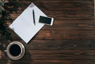 ノートとペンとiPhoneとコーヒー。観葉植物。左寄せ。の写真素材 [FYI01227712]