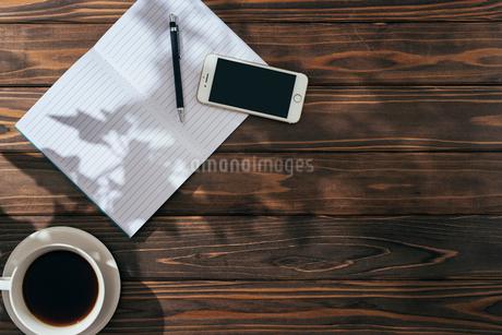 ノートとペンとiPhoneとコーヒー。木漏れ日。左寄せ。の写真素材 [FYI01227713]
