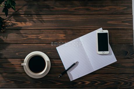 ノートとペンとiPhoneとコーヒー。引き。木目の背景。の写真素材 [FYI01227715]