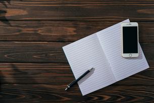 ノートとペンとiPhone。右寄せ斜め。木目の背景。の写真素材 [FYI01227716]