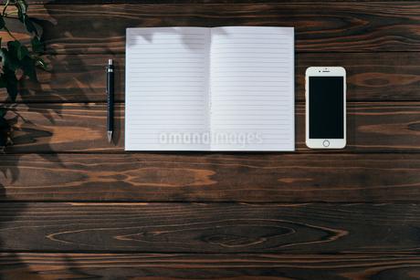 ノートとペンとiPhone。上寄せ。木目の背景。の写真素材 [FYI01227717]