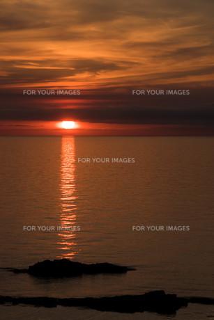 静かな海に沈む夕陽の写真素材 [FYI01227761]