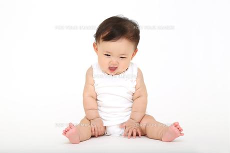 屋内白バックでお座りする新生児の赤ちゃん。新生児、赤ちゃん、育児、健康、愛、幸せイメージの写真素材 [FYI01227914]