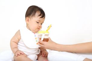 お母さんから飲み物をもらう乳幼児。赤ちゃん、育児、成長、健康、飲み物イメージの写真素材 [FYI01227921]