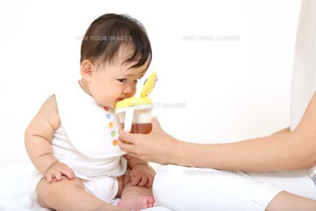 お母さんから飲み物をもらう乳幼児。赤ちゃん、育児、成長、健康、飲み物イメージの写真素材 [FYI01227922]