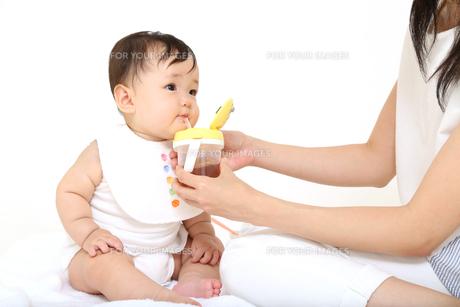 お母さんから飲み物をもらう乳幼児。赤ちゃん、育児、成長、健康、飲み物イメージの写真素材 [FYI01227923]