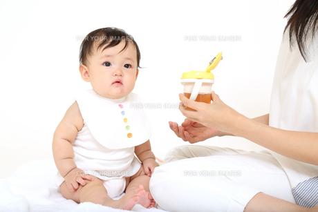 お母さんから飲み物をもらう乳幼児。赤ちゃん、育児、成長、健康、飲み物イメージの写真素材 [FYI01227924]