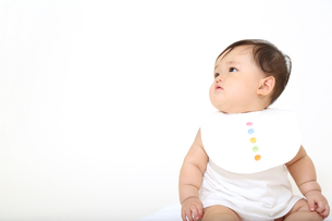 屋内白バックでお座りする新生児の赤ちゃん。新生児、赤ちゃん、育児、健康、愛、幸せイメージの写真素材 [FYI01227925]